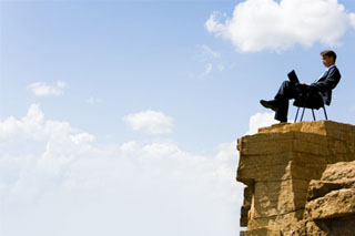 businessman sitting on a charge at the top of a precipitous ledge