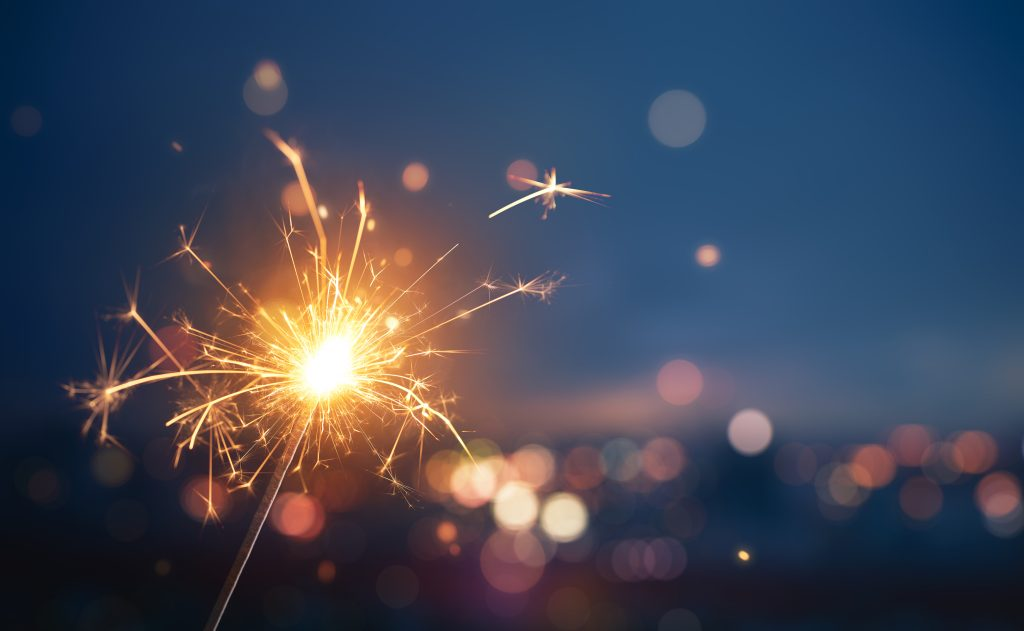 A sparkler firework with the blurred lights of a city in the distance behind it.