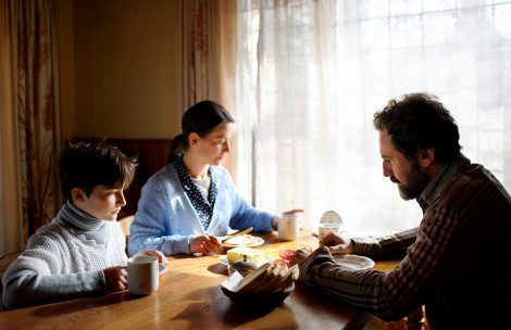A portrait of poor sad small girl with parents eating indoors at home, poverty concept.