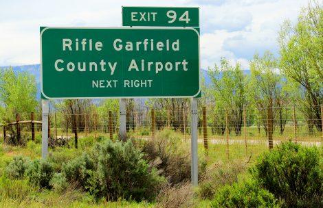 A sign showing the highway exit to the Rifle Garfield County Airport.