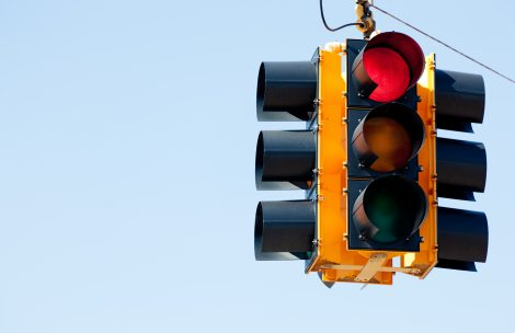 A red light traffic signal with blue sky copy space