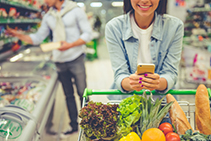 woman using phone to access the WIC app in grocery store